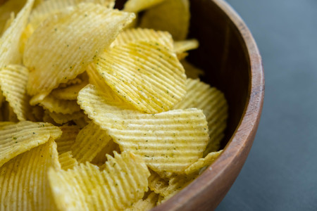 Potato chips in bowl on a grey background, top view. Salty crisps scattered on a table Stock Photo