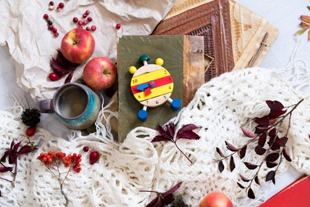 Fall Time Alarm clock on a rustic wooden table with colorful Autumn leaves. with light shadow and shallow depth of field. Daylight savings time concept. Autumn Time Change, with copy space. Top view