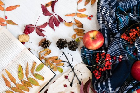 audio book: Hot coffee in mug with plaid or scarf, mobile phone with headphones, autumn leaf on a vintage table surface, selective focus.