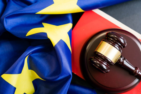 Judges wooden gavel with EU flag in the background. Symbol for jurisdiction. Wooden gavel on european union flag