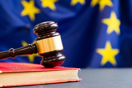 バック グラウンドで EU の旗を持つ裁判官木製小槌。管轄のシンボル。欧州連合の旗の木製小槌
