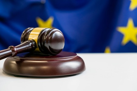 opinions: Judges wooden gavel with EU flag in the background. Symbol for jurisdiction. Wooden gavel on european union flag