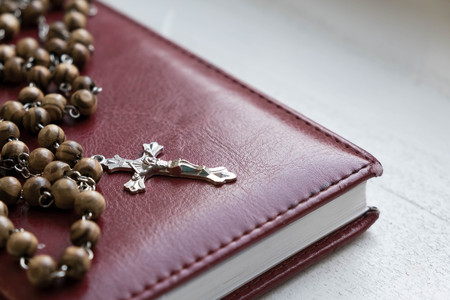 Closeup crucifix, Holy Bible and vintage rosary beads. Religion concept retro vintage color effect