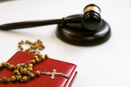 judges gavel and rosary beads on white background