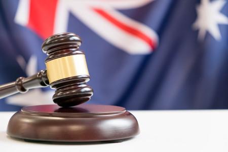 Gavel en juridisch boek op houten tafel, collage met vlag van Australië