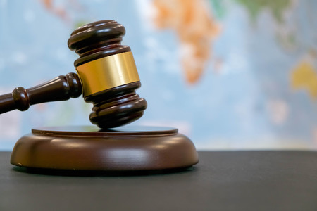 Judges gavel and over world map. Symbol for jurisdiction. Law concept a wooden judges gavel on table in a courtroom or law enforcement office on blue background. Copy space for text
