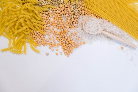 Set of products with complex carbohydrates on white background. wooden spoon, a range of cereals, pasta. Gluten free flour and cereals millet, green buckwheat, basmati rice,up view Archivio Fotografico