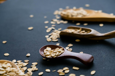 Oat stems and oat flakes in a wooden spoon on a dark background. Natural light. Selective focus. Close up on a black background. Top view, flat lay. copy space. dried grapes. Stock Photo