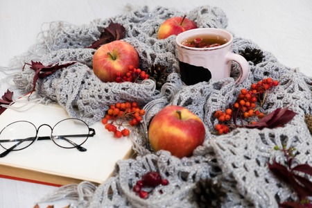 selective focus photo of grey cozy knitted scarf with cup tea and open book old wooden table. Stock Photo