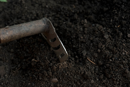 an old shovel stuck into the black earth dug in the garden. Stock Photo