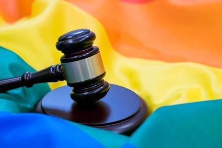 Hammer and gavel against against rainbow flag. gay flag background
