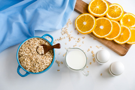 Oat flakes plate with milk, orange, eggs on a wooden white table. Top view of healthy oat flakes breakfast. Copy space
