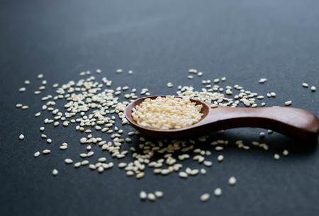 Organic natural sesame seeds wooden spoon. toasted sesame seeds. Raw, whole, unprocessed. Natural light. Selective focus. Close up on a black background. Top view, flat lay. copy space for text.
