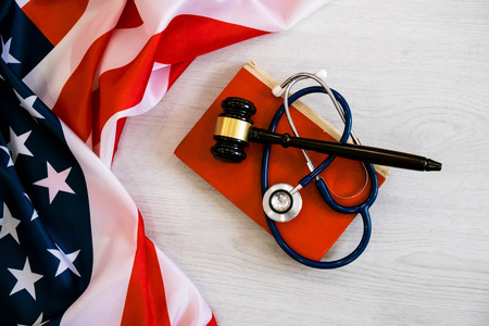 Gavel and stethoscope on national flag of USA. Forensic medicine concept Archivio Fotografico