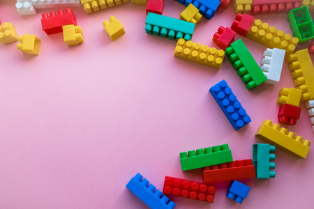 Close up Children plastic constructor. on a pink background stripe background. Developing toys