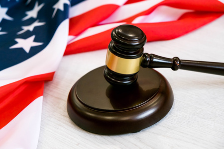 Wooden judge gavel and soundboard laying over US flag. Hammer and gavel. American law and justice concept. bidding concept. Stock Photo
