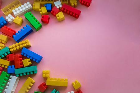 子供プラスチック コンス トラクターを閉じます。ピンク背景ストライプ背景。玩具を開発