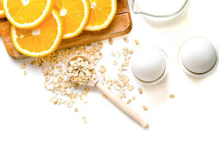 Oat flakes plate with milk, orange, eggs on a wooden white table. Top view of healthy oat flakes breakfast. Copy space. blue napkin Breakfast in bed plate, breakfast table buffet. Healthy ingredients