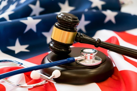 Gavel and stethoscope on national flag of USA. Forensic medicine concept