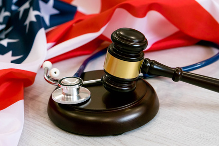 Gavel and stethoscope on national flag of USA. Forensic medicine concept Stock Photo