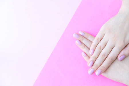 Stylish trendy female manicure. Beautiful young womans hands on pink and blue background.