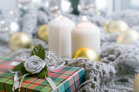 White holiday candles burning by silver tin star, Happy New Year and colorful ribbon on snowy rustic wooden background; holiday background with white copy space Stock Photo
