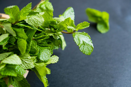 mint leaf. Green fresh mint, selective focus. Bunch of Fresh green organic mint leaf closeup. Peppermint. Natural light. Selective focus. Close up on a black background. Top view, flat lay. copy space Stock Photo