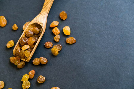 Raisins on a wooden spoon. Natural light. Selective focus. Close up on a black background. Top view, flat lay. copy space