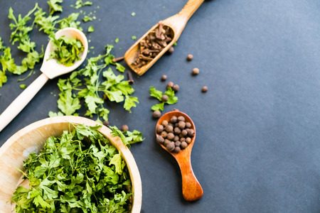 black pepper in spoon, parsley herb. Close up on a black background. Top view, flat lay. copy space. dried grapes