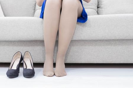 Onderneemster die hoge hielenschoenen na het werk thuis opstijgen Stockfoto