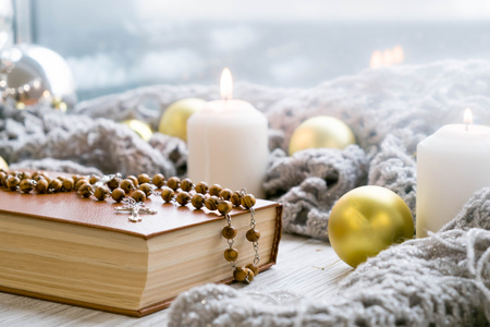 White holiday candles glowing behind wooden cross with red hearts in snow by antique rustic wood background; Christmas, Easter and religious background with copy space Stock Photo