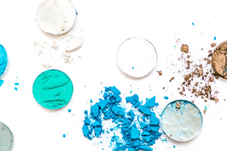 Samples of dry blush, powder, bronzers and highlighter scattered in a line isolated on a white background Stock Photo