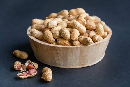 Raw peanuts in bowl on a black wooden table.