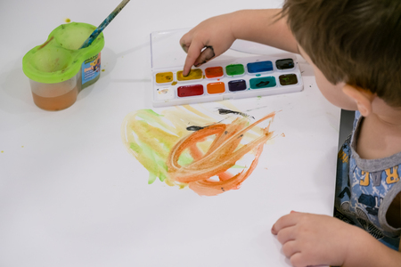 the kid is painting in kindergarten. educational classes for a toddler of two years Stock Photo