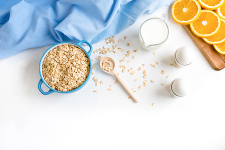 Oat flakes plate with milk, orange, eggs on a wooden white table. Top view of healthy oat flakes breakfast. Copy space. blue napkin Breakfast in bed plate, breakfast table buffet. Healthy ingredients.