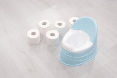 青い背景に青いトイレットの横に白いトイレットペーパーとおむつのスタック