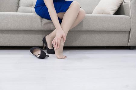 ヘルスケアの概念。痛みを伴う足をマッサージする女性、痛み領域に赤い光を当てた 写真素材