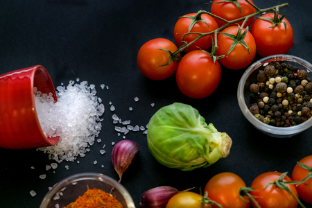 Close up of colorful spices and fresh vegetables for cooking on dark metal background with space for text. Top view. Bio Healthy food ingredients. Stock Photo