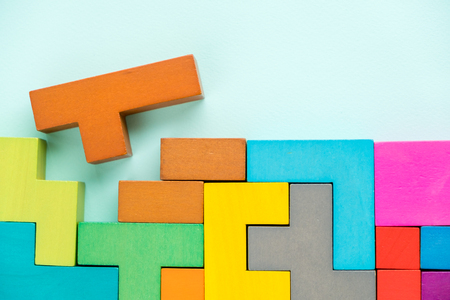Different colorful shapes wooden blocks on beige background, flat lay. Geometric shapes in different colors, top view. Concept of creative, logical thinking or problem solving. Copy space. Archivio Fotografico