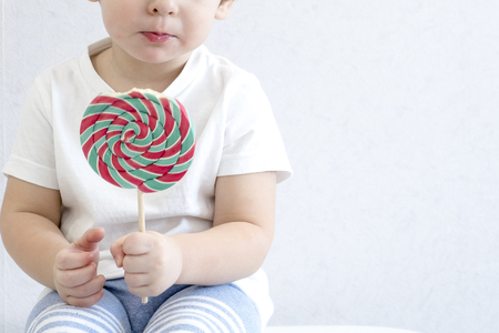 Fashion baby boy. Trendy boy with lollipop. funny cute little infant in white t-shirt. care of teeth, danger of tooth decay. Asian baby 2 years old. Happy kid with a big candy. Small child