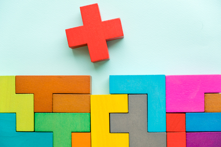 Different colorful shapes wooden blocks on beige background, flat lay. Geometric shapes in different colors, top view. Concept of creative, logical thinking or problem solving. Copy space. Foto de archivo