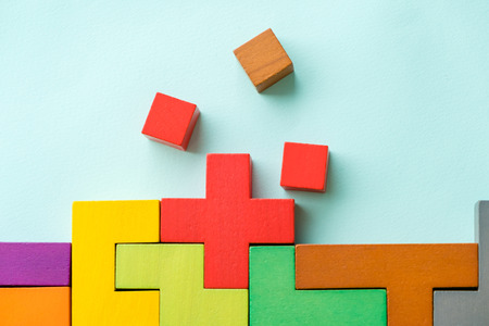 Different colorful shapes wooden blocks on beige background, flat lay. Geometric shapes in different colors, top view. Concept of creative, logical thinking or problem solving. Copy space. Stock Photo