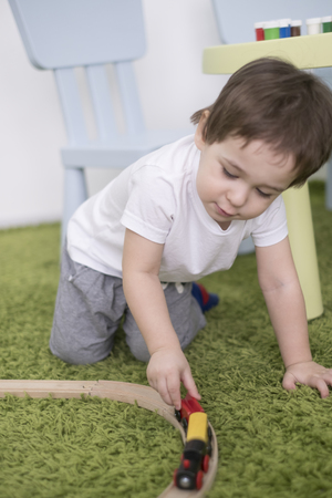 Small toddler in a colorful children room in a nursery or preschool. child boy playing with toys indicators at home. Asian baby 2 years old plays alone on a green carpet.