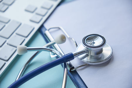 Stethoscope with clipboard and Laptop on desk,Doctor working in hospital writing a prescription, Stock Photo
