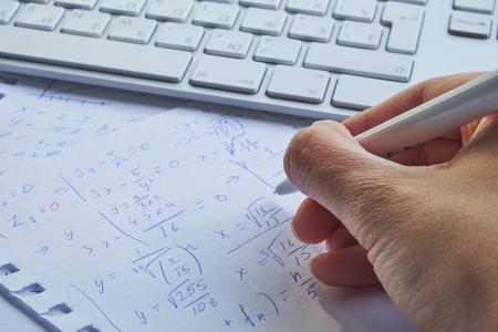 feuille de papier remplie de calculs en arrière-plan. Problèmes de mathématiques sur graphique avec un crayon. Faire de l'algèbre