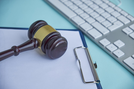 Wooden gavel and keyboard on desk