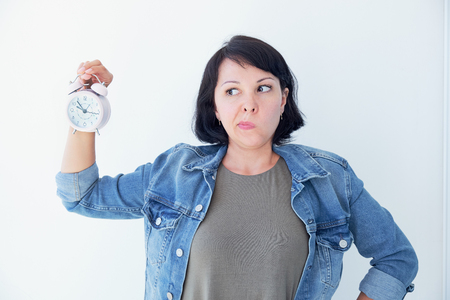 Asian woman holding a pink alarm clock on a white background. the concept of time management. get control of your life Foto de archivo