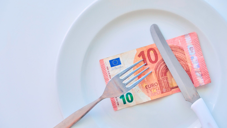 Euro banknote on a white plate, cash in Europe, the cost of lunch in the restaurant Banco de Imagens