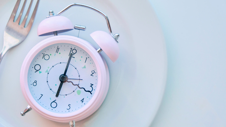 reloj en un plato vacío, fondo blanco. el concepto de limitar la ingesta de alimentos.