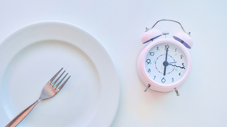 clock on an empty plate, white background. the concept of limiting the intake of food.